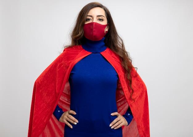 Selbstbewusstes kaukasisches superheldenmädchen mit rotem umhang, das rote schutzmaske trägt