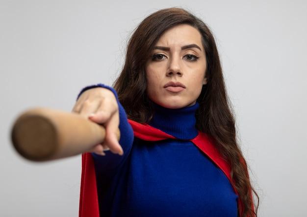 Selbstbewusstes kaukasisches superheldenmädchen mit rotem umhang hält baseballschläger auf weiß aus