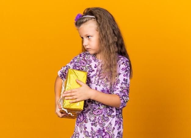 Selbstbewusstes kleines blondes mädchen, das eine geschenkbox hält und die seite isoliert auf der orangefarbenen wand mit kopienraum betrachtet