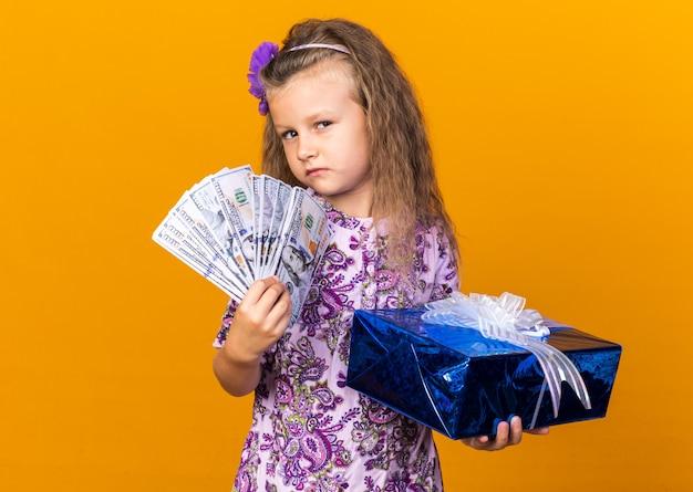 Selbstbewusstes kleines blondes mädchen, das geschenkbox und geld lokalisiert auf orange wand mit kopienraum hält