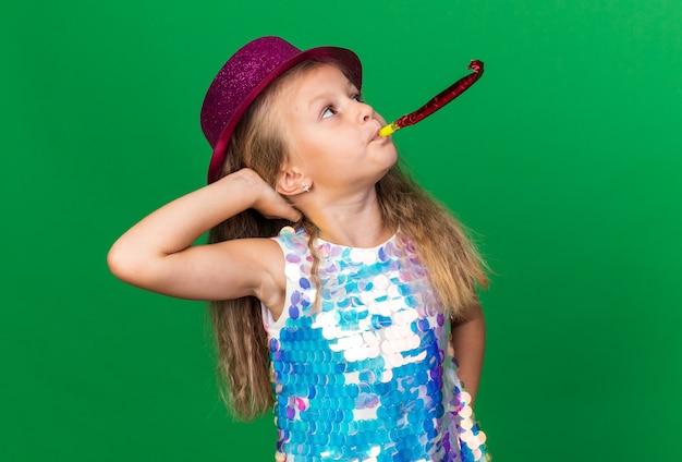 Selbstbewusstes kleines blondes mädchen mit lila partyhut, das partypfeife bläst und aufschaut, die hand auf den kopf legen, isoliert auf grüner wand mit kopierraum