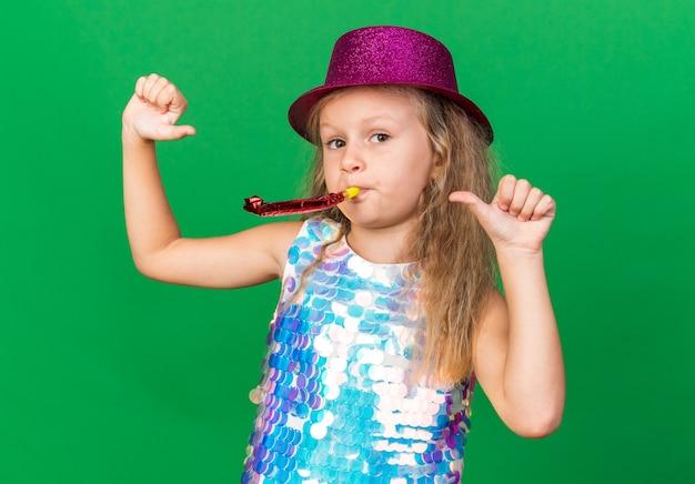 Selbstbewusstes kleines blondes mädchen mit lila partyhut, der partypfeife bläst und auf sich selbst zeigt, isoliert auf grüner wand mit kopierraum