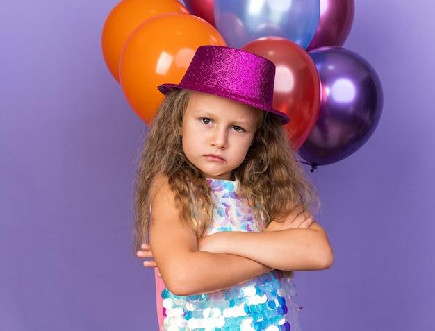 Selbstbewusstes kleines blondes mädchen mit violettem partyhut, das mit verschränkten armen vor heliumballons steht, lokalisiert auf lila wand mit kopienraum