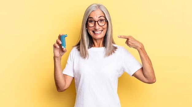 Selbstbewusstes lächeln, das auf das eigene breite lächeln, positive, entspannte, zufriedene haltung zeigt. asthma-konzept