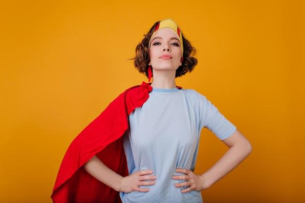 Selbstbewusstes lockiges mädchen in der superheldenkleidung, die auf hellgelbem raum aufwirft