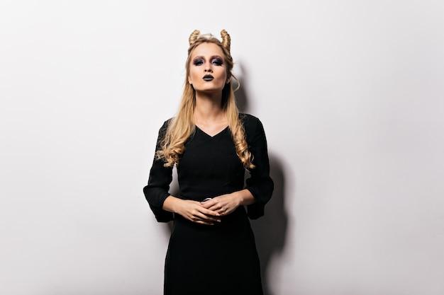 Selbstbewusstes mädchen im hexenkostüm, das sich auf karneval vorbereitet. blonde ernsthafte dame mit vampir-make-up, das in halloween aufwirft.