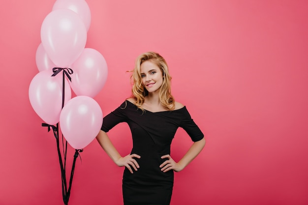 Selbstbewusstes mädchen im schönen kleid, das ereignis genießt. interessierte blonde dame mit rosa luftballons, die glück ausdrücken.