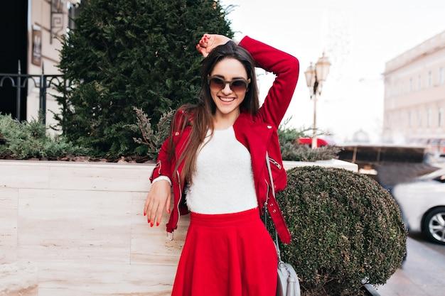 Selbstbewusstes mädchen in roter kleidung, das mit dem glückseligen lächeln aufwirft