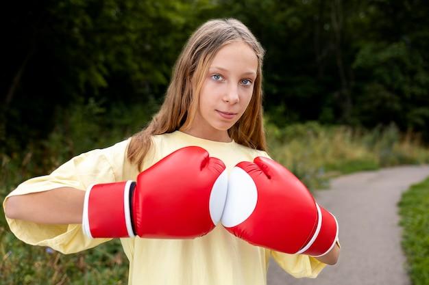 Selbstbewusstes mädchen mit boxhandschuhen