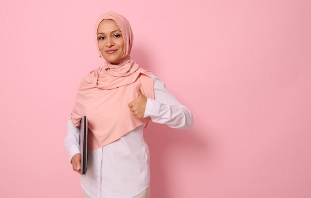 Selbstbewusstes porträt einer erfolgreichen wunderschönen arabischen muslimin in rosa hijab und strenger freizeitkleidung, die einen daumen nach oben zeigt, in die kamera schaut und vor farbigem pastellhintergrund mit platz für text posiert