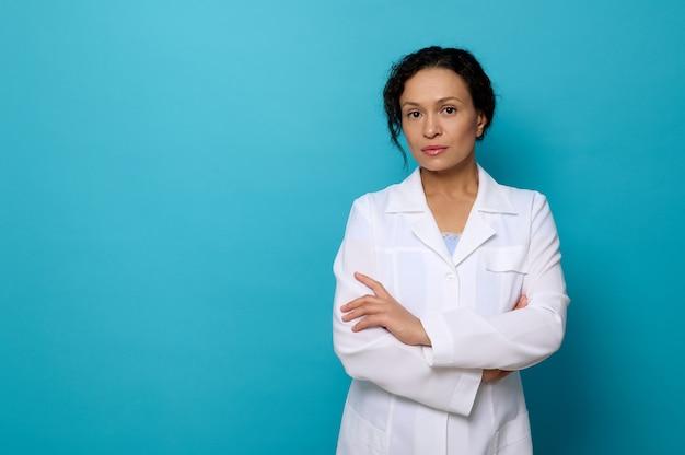 Selbstbewusstes porträt einer schönen, ruhigen ärztin in weißem medizinischem kittel, mit blick auf die kamera, die mit verschränkten armen vor blauem hintergrund mit kopienraum für medizinische werbung posiert