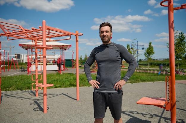Selbstbewusstes porträt eines gutaussehenden kaukasischen sportlers, der auf dem sportplatz mit armen auf der taille steht und lächelnd in die kamera schaut. hübscher kaukasischer typ in sportkleidung, der sich nach dem training ausruht