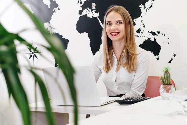 Selbstbewusstes reisebüro mit laptop im büro für die online-kommunikation