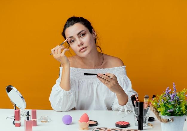 Selbstbewusstes schönes mädchen sitzt am tisch mit make-up-werkzeugen, die make-up-pinsel und lidschatten-palette halten, die lokal auf orange wand schauen
