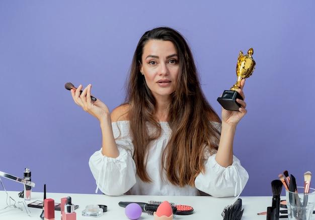 Selbstbewusstes schönes mädchen sitzt am tisch mit make-up-werkzeugen hält make-up-pinsel und gewinner-tasse isoliert auf lila wand
