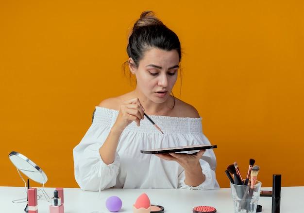 Selbstbewusstes schönes mädchen sitzt am tisch mit make-up-werkzeugen hält make-up-pinsel und schaut auf lidschatten-palette isoliert auf orange wand