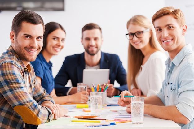 Selbstbewusstes und kreatives team. gruppe fröhlicher geschäftsleute in eleganter freizeitkleidung, die zusammen am tisch sitzen und in die kamera schauen