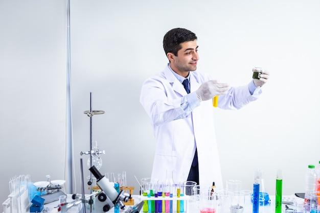 Selbstbewusstes wissenschaftlerporträt eines glücklichen männlichen wissenschaftlers in einem chemielaborwissenschaftler, der reagenzglas mit probe im hintergrund der laboranalyse hält