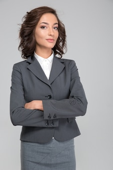 Selbstgefällige priggish versicherte erfolgreiche junge lockige geschäftsfrau im grauen anzug mit verschränkten armen
