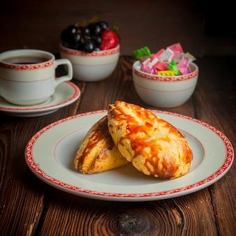Selbstgemachte bäckerei der seitenansicht-nahaufnahme mit tasse tee, süßigkeiten und beeren auf holztisch