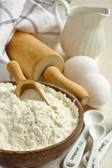 Selbstgemachte glutenfreie mehlmischung aus reismehl, hirsemehl, kartoffelstärke und xanthangummi in holzschale mit messlöffel