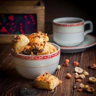 Selbstgemachte kekse der seitenansicht-nahaufnahme mit tasse tee auf holztisch
