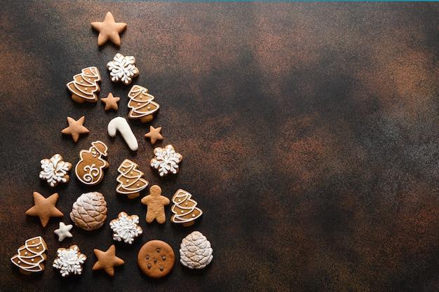 Selbstgemachte kekse der weihnachtsferien angeordnet als baum auf braun