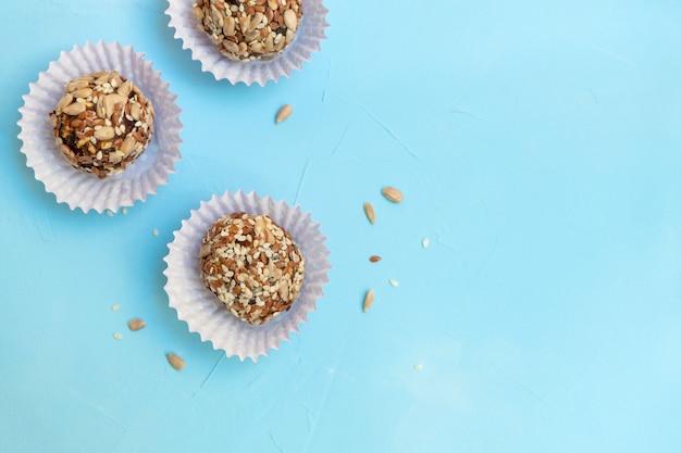Selbstgemachte natürliche süßigkeiten-energiekugeln auf pastellblauem tisch.