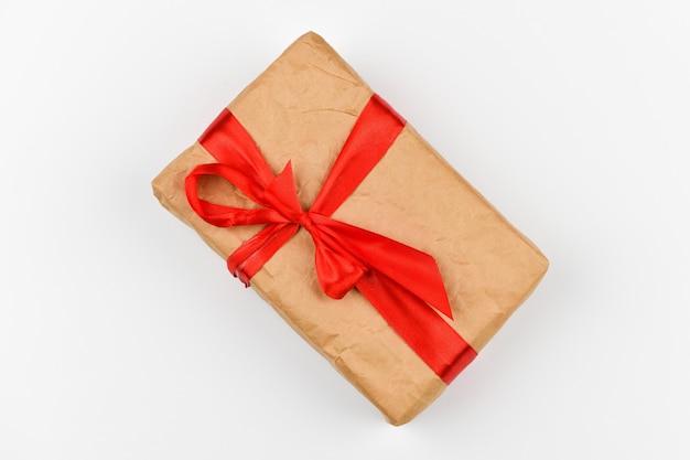 Selbstgemachte papiergeschenkverpackung mit einer roten schleife auf einem weißen raum. nadelgrüne zweige auf einem weißen raum. sicht von oben. platz zum schreiben. weihnachtsraum.