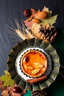 Selbstgemachte rustikale kürbiskuchen des herbstnahrungsmittelkonzepts verzieren durch herbsturlaub auf schwarzem hintergrund mit kopienraum