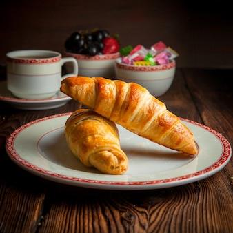 Selbstgemachtes croissant der nahaufnahme mit tasse tee, süßigkeiten und beeren auf holztisch