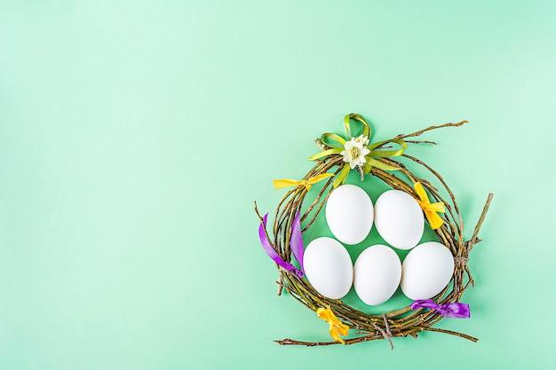 Selbstgemachtes handwerksnest von zweigen und bunten bändern mit weißen eiern auf grünem hintergrund. ostern tischdekoration. osterfestkomposition mit kopierraum für text.