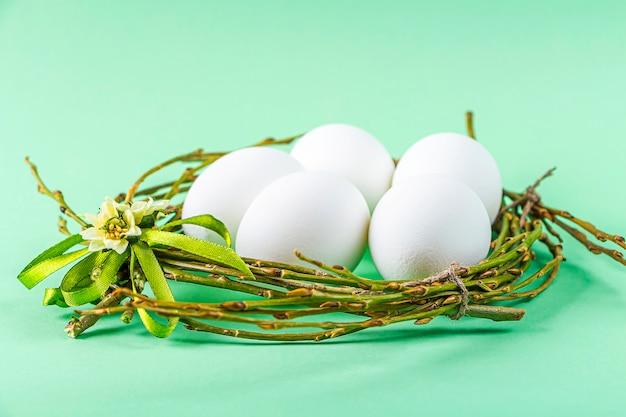 Selbstgemachtes handwerksnest von zweigen und bunten bändern mit weißen eiern auf grünem hintergrund. ostern tischdekoration. osterfestkomposition.