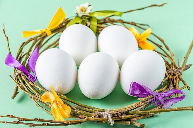 Selbstgemachtes handwerksnest von zweigen und bunten bändern mit weißen eiern auf grünem hintergrund. ostern tischdekoration. osterfestkomposition,