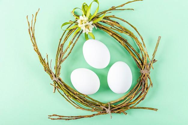 Selbstgemachtes handwerksnest von zweigen und bunten bändern mit weißen eiern auf grüner oberfläche. ostern tischdekoration. osterfestkomposition mit kopierraum für text.