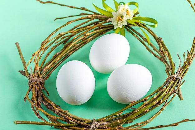Selbstgemachtes handwerksnest von zweigen und bunten bändern mit weißen eiern auf grüner oberfläche. ostern tischdekoration. osterfestkomposition.