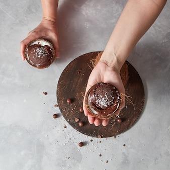 Selbstgemachtes schokoladendessert in einer kokosnussschale, die frauenhände über rundem brett auf einem grauen tisch mit platz für text hält. sommerdessert.