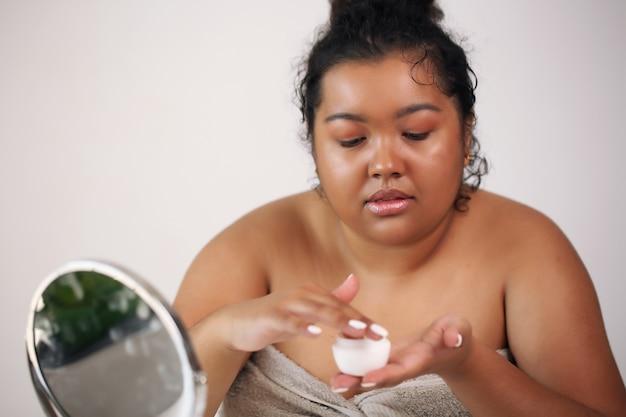 Selbsthilfe. schöne afroamerikanerfrau im bademantel bereit, make-up aufzutragen,