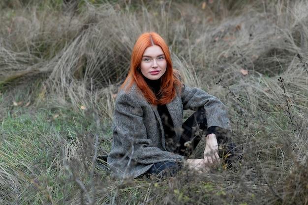 Selbstisolation im freien. mädchen, das allein im grünen wald sitzt, genießt die stille und schönheit der natur.