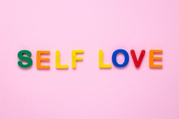 Selbstliebetext auf rosa papierhintergrund gemacht von den bunten plastikbuchstaben.