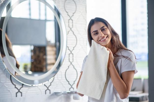 Selbstpflege. eine frau trocknet ihre haut mit einem handtuch nach spa-eingriffen