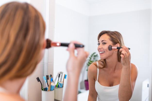 Selbstpflege und make-up-konzept. taillenreflexion im spiegel der jungen lächelnden frau im weißen bademantel, der auf puder-rouge unter verwendung der bürste legt