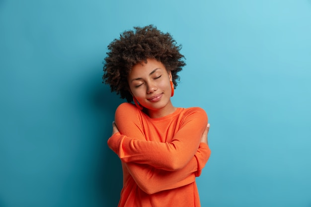 Selbstpflege- und zärtlichkeitskonzept. erfreute dunkelhäutige frau umarmt sich, hält schultern, fühlt sich in ihrem neuen pullover wohl, hat romantische zarte stimmung, braucht wärme, komfort und liebe