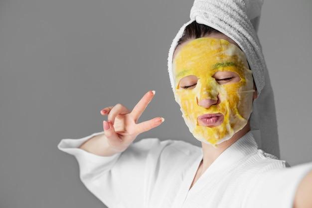 Selbstpflegekonzeptfrau mit gesichtsmaske hautnah