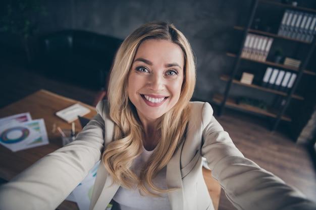 Selbstporträt der fröhlichen zahnig strahlenden geschäftsdame, die selfie in ihrem büro nimmt