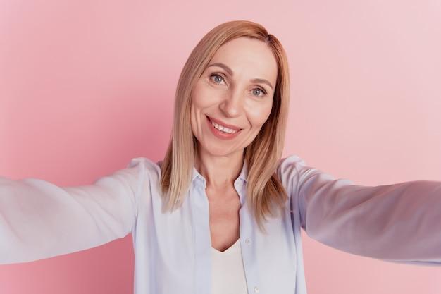 Selbstporträt einer hübschen jungen frau in lässigem outfit, die ein selfie auf der frontkamera auf rosafarbenem hintergrund schießt