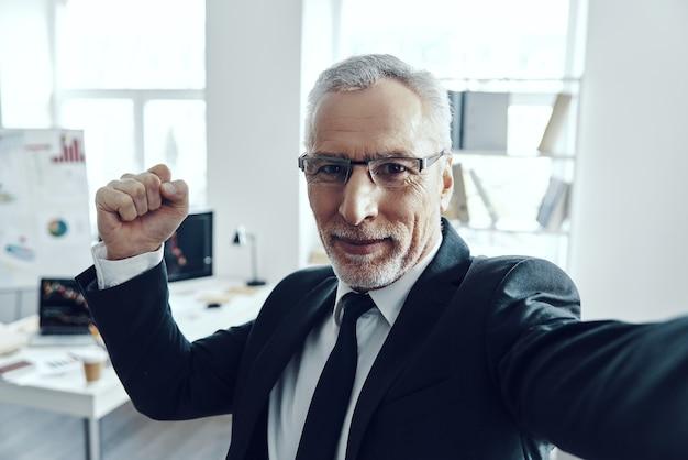 Selbstporträt eines älteren mannes im eleganten business-anzug, der die kamera anschaut und lächelt, während er im büro steht