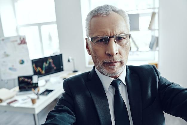 Selbstporträt eines älteren mannes im eleganten business-anzug, der im büro in die kamera schaut
