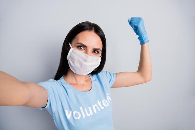 Selbstporträt von ihr sie schöne attraktive mächtige erfolgreiche erfolgreiche starke freiwillige sozialarbeiterin zeigt muskeln retten welt globale lösung über grau pastell farbe hintergrund isoliert