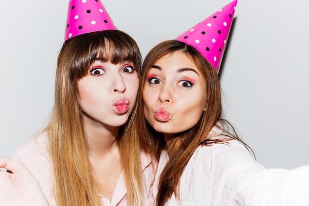 Selbstporträt von zwei frauen in rosa papiergeburtstagshüten. freunde tragen rosa pyjama und senden kuss. verspielte stimmung.